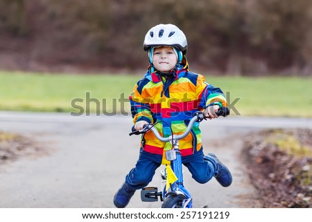 Funny cute  preschool kid boy in safety helmet and colorful raincoat riding his first bike and having fun on cold  day, outdoors. Active leisure with children in winter, spring or autumn. - stock photo