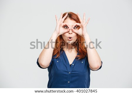 Funny cute redhead young woman looking throug glasses made of fingers over white background - stock photo