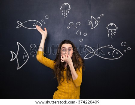 Funny cute young woman closed nose by hand and simulating deep diving under the sea over blackboard background - stock photo
