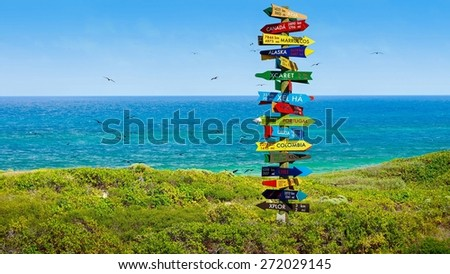 Funny direction signpost with distance to many different countries - stock photo