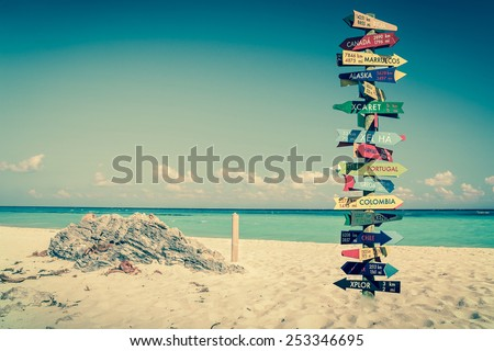 Funny directions signpost with distance to many different countries - stock photo