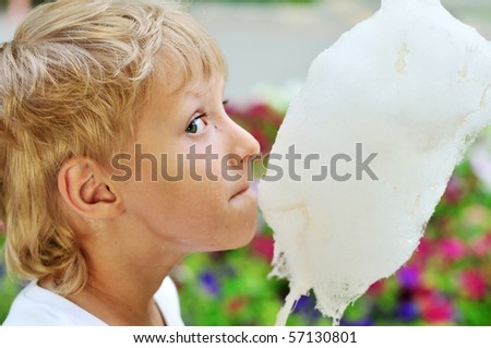 funny dirty face of little boy eating sweet cotton candy - stock photo