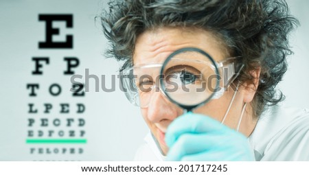 Funny doctor ophthalmologist looks through a magnifying glass on a background of eyesight test chart - stock photo
