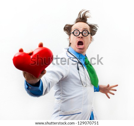 Funny doctor with heart in hand - stock photo
