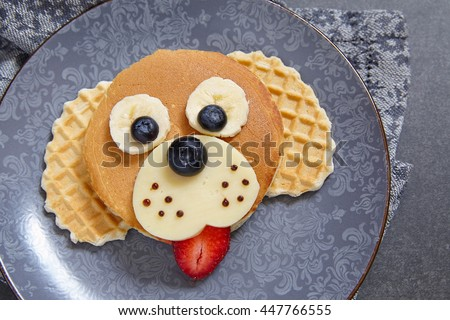 Funny dog pancake with berries for kids breakfast - stock photo