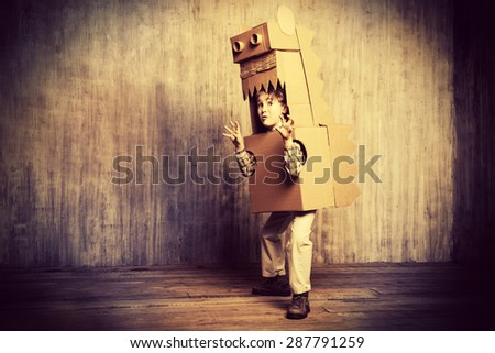 Funny dreamer boy playing with a cardboard dragon, dinosaur. Childhood. Fantasy, imagination. Retro style, sepia. - stock photo