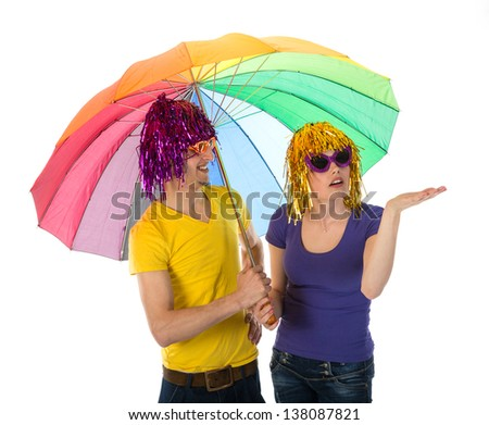 Funny dressed couple with umbrella looking for rain - stock photo