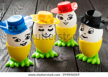 Funny easter eggs with a smile on the face in colorful hats on a dark wooden table - stock photo