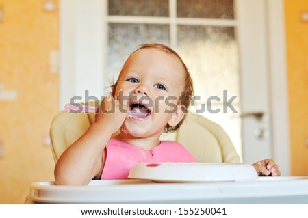 funny  eating baby girl with dirty face - stock photo