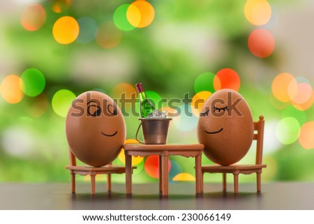 funny eggs on a beach chair relaxing  with christmas tree bokeh behind - stock photo