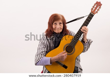 Funny elderly lady plays passionate on a classic acoustic guitar
