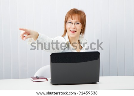 funny employee office. Woman with laptop points a finger in the direction of - stock photo