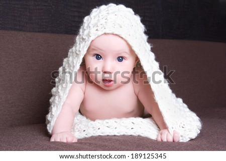funny excited baby girl in white woolen scarf crawling - stock photo