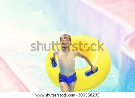 Funny excited child enjoying summer vacation in water park riding on slide with yellow float laughing. - stock photo