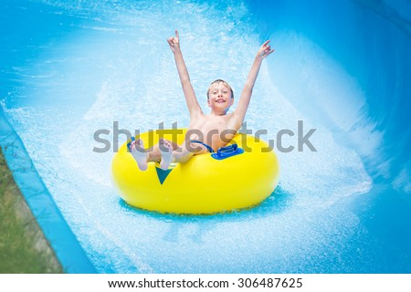 Funny excited child enjoying summer vacation in water park riding yellow float laughing. - stock photo