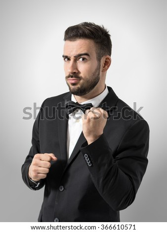 Funny expression of new groom holding clenched fist gesture with wedding ring. Portrait over gray studio background.  - stock photo