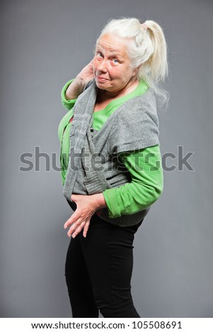 Funny expressive senior woman. Acting young. Studio shot isolated on grey background. - stock photo