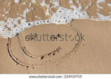 funny face  drawning  on  sand near  sea - stock photo