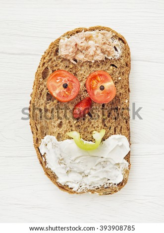 Funny face made of bread, butter, tuna, sausage, tomato and black pepper. Humorous food. - stock photo