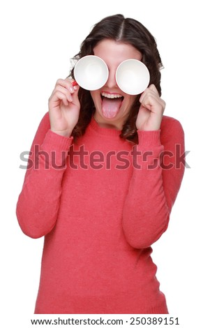 Funny face of a young girl wearing casual clothes and holding red coffee cup on white background - stock photo