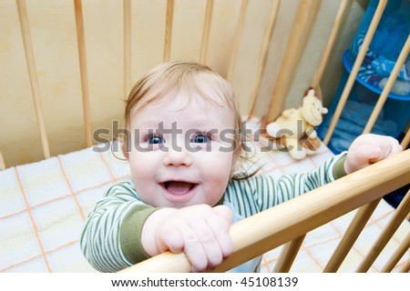 Funny face of baby boy playing in bed