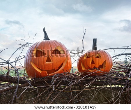 Funny face pumpkins sitting on grapevine and fence - stock photo