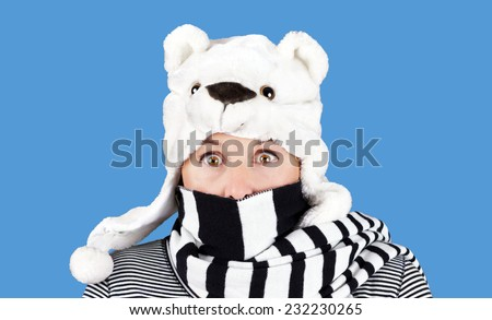 Funny face woman with polar bear hat and stripe scarf: humorous winter concept - stock photo
