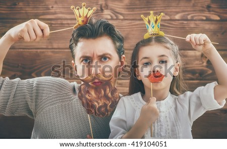 Funny family! Father and his child daughter girl with a paper accessories. Beauty funny girl holding paper lips and crown on stick. Beautiful young man holding paper beard and crown on stick. - stock photo