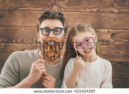 Funny family! Father and his child daughter girl with a paper accessories. Beauty funny girl holding paper glasses on stick. Beautiful young man holding paper beard and glasses on stick. - stock photo