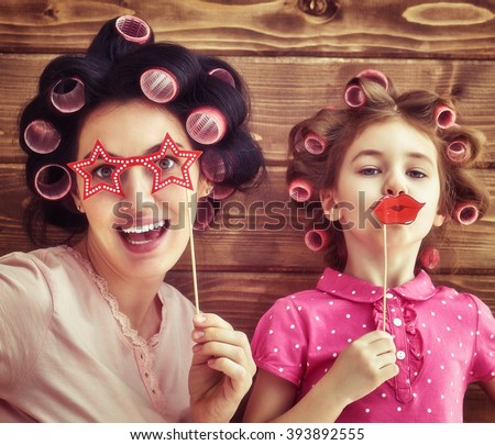 Funny family! Mother and her child daughter girl with a paper accessories. Beauty funny girl holding paper lips on stick. Beautiful young woman holding paper glasses on stick. - stock photo