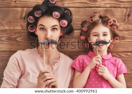 Funny family! Mother and her child daughter girl with a paper accessories. Beauty funny girl holding paper mustache on stick. Beautiful young woman holding paper mustache on stick. - stock photo