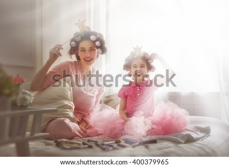 Funny family! Mother and her child daughter girl with a paper accessories. Mother and daughter preparing for a party and having fun. Beautiful young woman and funny girl with a paper crowns on sticks. - stock photo
