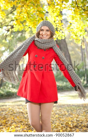 funny fashion girl in autumn clothes posing in  park