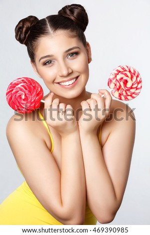 Funny fat teenage girl eating big lollipop. Happy teenager with colorful caramel candy bonbon isolated on white background in studio. Unhealthy food diet and lifestyle concept.