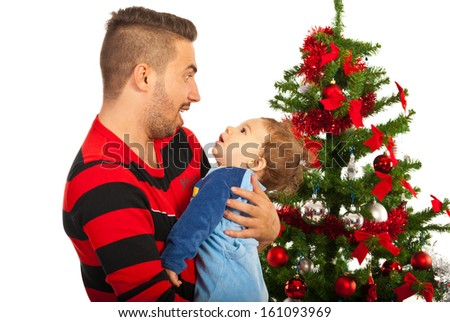 Funny father with baby boy in front of Christmas tree - stock photo