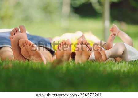 funny feet of young family laying in park - stock photo
