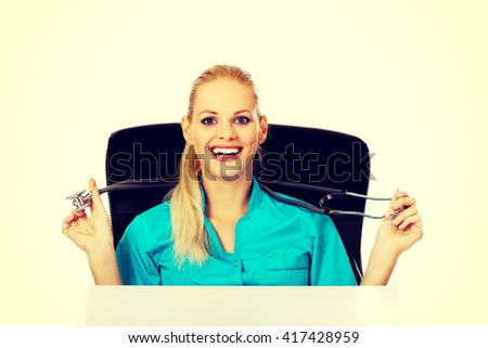 Funny female doctor or nurse sitting behind the desk with stethoscope - stock photo