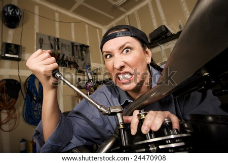 Funny female Hispanic mechanic  working on a chopper style motorcycle - stock photo