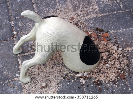 Funny figurine of digging dog - stock photo