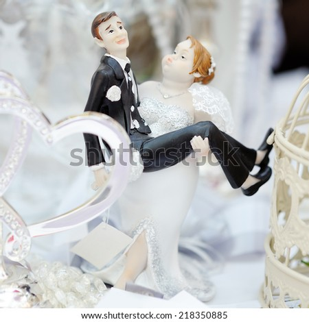 Funny figurines bride and groom on top of wedding cake - stock photo