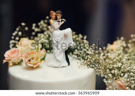 Funny figurines suite at a luxury wedding white cake decorated with fresh flowers. - stock photo