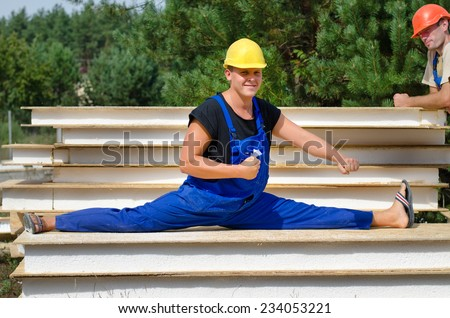 Funny fit worker wearing blue overalls and protection yellow hard hat while sitting in side split position on a pile of boards, during a break at work, outdoor, in a construction site, in summer - stock photo