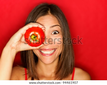 Funny food woman with red tomato smiling happy. Healthy eating and vegetables concept photo with fresh cute multiracial mixed race Asian Caucasian female model on red background. - stock photo
