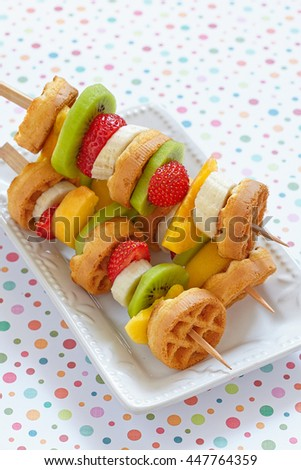 Funny fruits and berries kebab on a dish