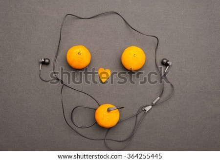 Funny fruity music player: headphones coming from of mandarin on a black background. Small orange heart and two mandarins lying near him in the form of face. Present for music and fruit lovers. - stock photo