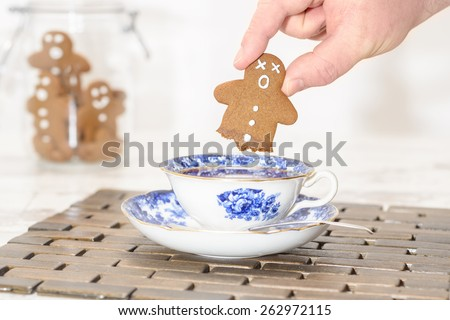 Funny gingerbread man with no legs after being dipped into hot tea - stock photo