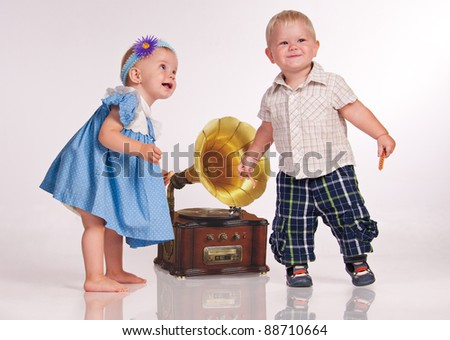 Funny girl and a boy dancing near the gramophone. - stock photo