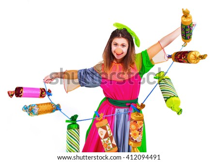Funny girl clown holding a candy toys, isolated on a white background. Clown in the costume - stock photo