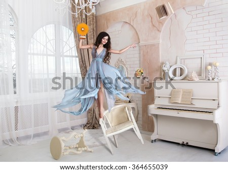 funny girl clowns jumping on chairs and holding a fan,fashionable toning,creative computer colors - stock photo