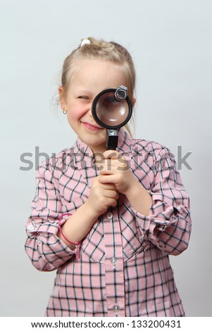 Funny girl explores with a magnifying glass. - stock photo